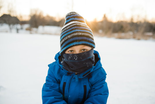 Young boy looking at camera with blue scarf and winter hat.