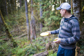 Man prepares to throw frisbee during a disk gold game in the forest.
