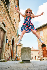 Cute girl jumping on sidewalk in old town in Italy