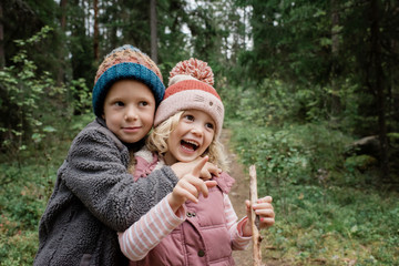 brother hugging his sister laughing whilst walking through the forest