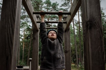 boy playing on monkey bars climbing on a outdoor fitness course
