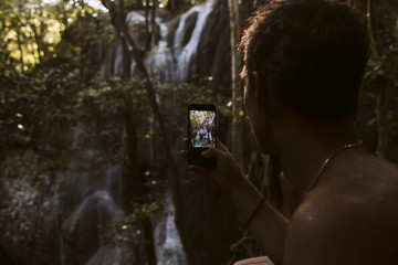 Cropped image of man photographing waterfall in forest