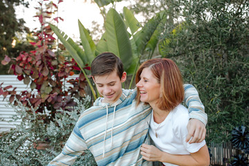 Smiling teen boy hugging laughing mom in front of lush plants