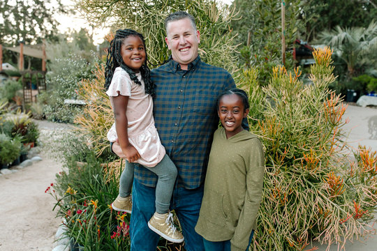 Joyful white dad holding one daughter and hugging other daughter