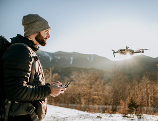 A man with a beard flies a drone in the mountains in winter.