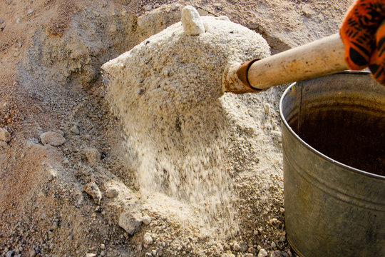 Loading sand with a shovel into a bucket