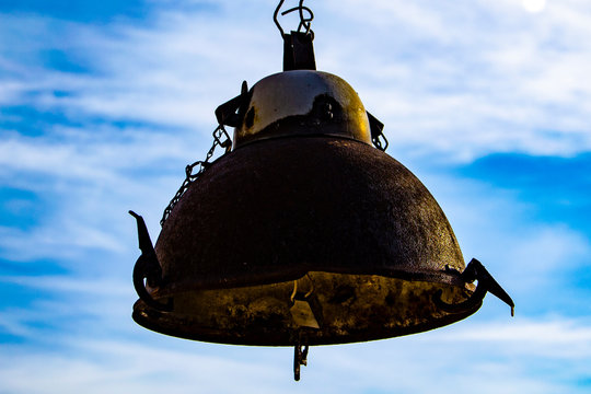 Old, rusty lantern hanging on a sky background
