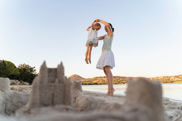 Sand castle and happy mother with daughter on the beach