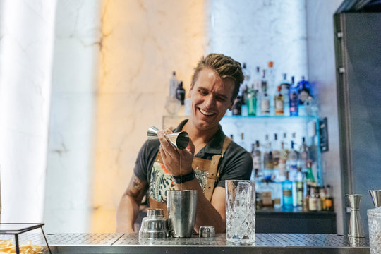 Bartender mixing cocktail in a bar, using jigger