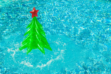 Inflatable Christmas tree splashing out of sparkling blue swimming pool in a bright tropical holiday travel background