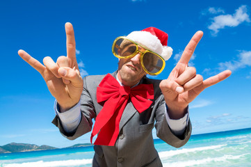 Funky businessman in Santa hat, sunglasses and big red Christmas bow making rock n roll gestures on a tropical beach