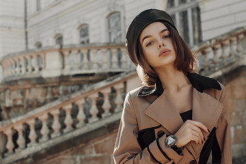 Outdoor autumn fashion portrait of young elegant lady wearing trendy faux leather beret, classic beige trench coat, wrist watch, posing in street of European city. Copy, empty space for text Wall mural
