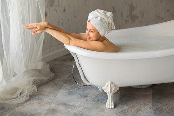 beautiful young woman with a towel on her head washes in a bath with milk Wall mural