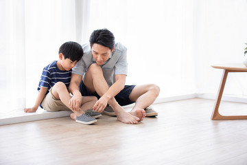 Chinese father teaching his son to tie shoelaces Wall mural