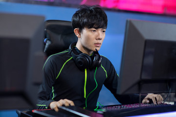 Young Chinese man playing esports