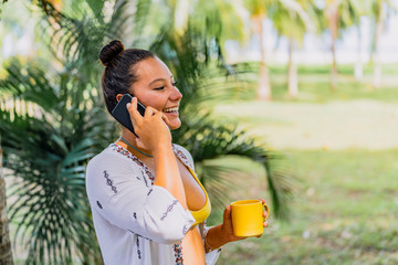 Happy woman speaking on smartphone looking away while holding mug and standing on sunny lawn by palm tree in Costa Rica