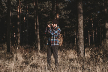 Confident photographer taking picture with camera in sunny forest
