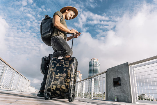 Traveller man texting phone with his luggage walking on Ocean drive South Beach Florida. Traveller concept