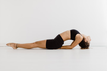 Sportive woman performing yoga pose in room