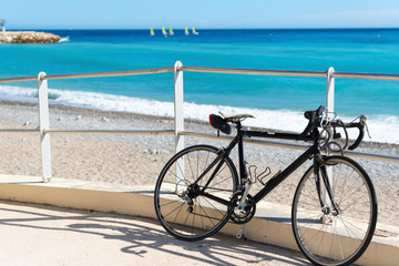 A bicycle sits parked along a ramp to the beach as a group of matching sailboats are blurred in the distance on the French Riviera in Menton, France