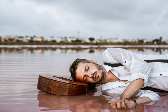 Sleepy man in white shirt and suspenders lying down with closed eyes with head resting at an acoustic guitar in sea at sandbank