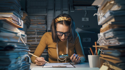 Businesswoman checking a contract with a magnifier