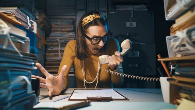 Stressed secretary shouting at the telephone receiver