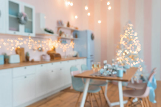 Defocused blurry Interior of modern white kitchen with pink walls and blue decor on a Christmas New year eve