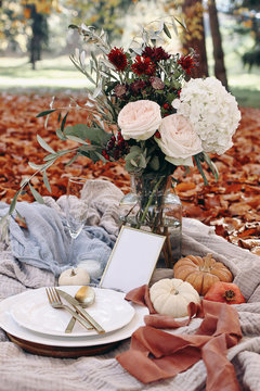 Autumn wedding table setting. Garden party celebration, picnic with golden cutlery, porcelain plate,wine glass and white pumkins. Rose flowers bouquet with olive branches. Red beech leaves ground.