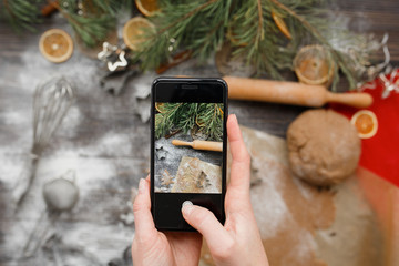 Female hands holding a phone and taking a picture of Christmas cookies while cooking. Top view, flat lay. Christmas mood, winter  holiday mockup.