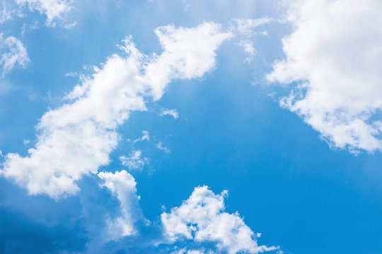 blue sky with puffy clouds. beautiful springtime nature background. dynamic side lit cloudscape
