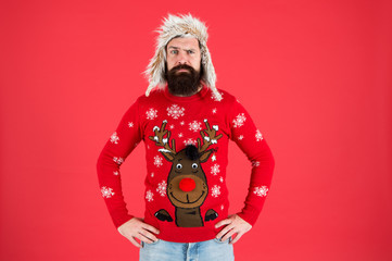 Buy festive clothing. Sweater with deer. Hipster bearded man wear winter sweater and hat. Happy new year. Join holiday party craze and host Ugly Christmas Sweater Party. Winter party outfit