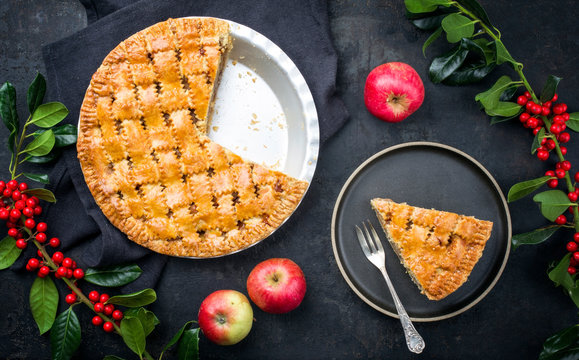 Traditional apple jalousie cake offered as top view on a modern design plate and backing form with decoration on a black board