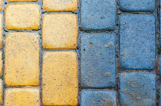 yellow and blue cobbles of pavement texture. stone masonry floor covering close up. top view of vertical wet grungy background