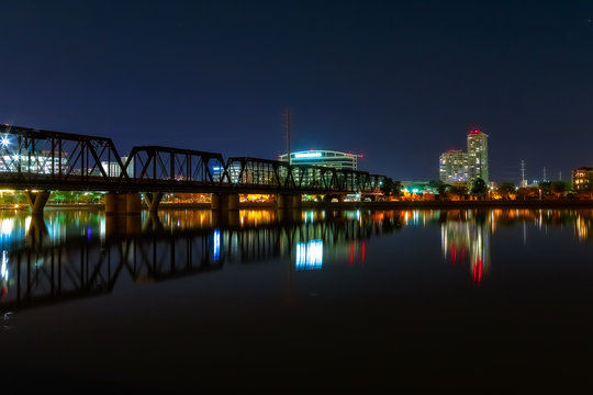 Symmetrical, reflective, night time view of one part of Tempe Town lake, AZ, with the office buildings in the backdrop and rail bridge.