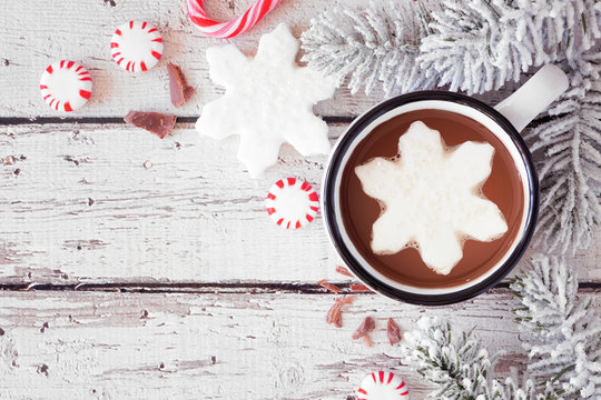 Hot chocolate with snowflake marshmallow. Top view corner border with snowy branches and candy against a white wood background with copy space.