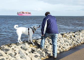Mann mit Hund an der Nordsee bei Cuxhaven, Spaziergang mit Husky an der Nordseeküste