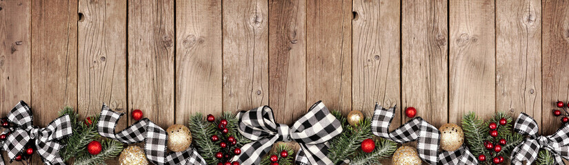 Wall Mural - Christmas border banner with white and black checked buffalo plaid ribbon, ornaments and tree branches. Above view on a rustic wood background.
