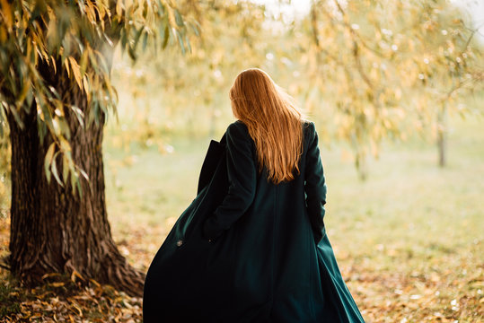 beautiful young girl with red hair and in long coat is resting in the park, woman walking outdoors
