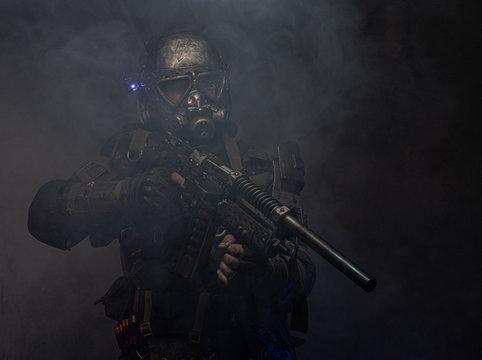 Dark post apocalypse knight is posing for photographer in light smoke.