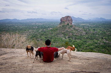 The unspecific man and his dogs play together on a rock admires the beautiful views at  Pidurangala mountain. Sri Lanka.