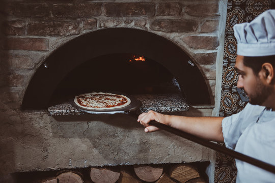 Italian chef is putting gourmet freshly made pizza to the stone oven.