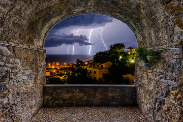 Rock balcony overlooking a lightning storm over the sea