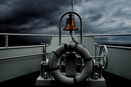 A lifesaver ring and a golden bell on a boat sailing the ocean during a mischievous stormy weather