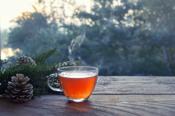 Photo sur Aluminium The Cup with hot steaming tea on a rustic wooden garden table with Christmas decoration on a winter day, health concept against cold and flu, copy space,