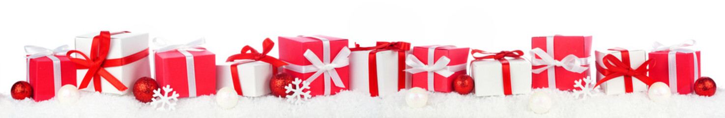 Wall Mural - Christmas border of red and white gift boxes in snow. Side view isolated on a white background.