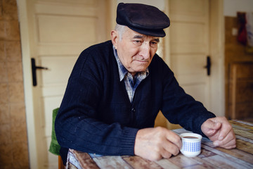 Senior man grandfather old pensioner farmer wearing black sweater and hat having a cup of coffee or tea by the table at home sitting alone