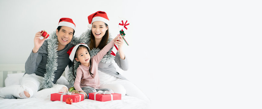 Asian family have father, mother and daughter with gray, pink casual wear and Santa hats. Sitting on a white bed with a red gift box And  small ball. Celebrate Christmas and Happy New Year. copy space