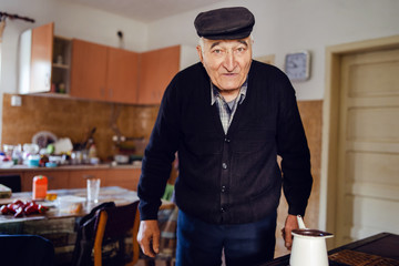 Senior man grandfather old pensioner farmer wearing black sweater and hat having a cup of coffee or tea cooking in the pot at home waiting to boil