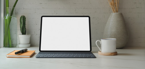 Wall Mural - Close-up view of blank screen digital tablet with books and office supplies with coffee cup